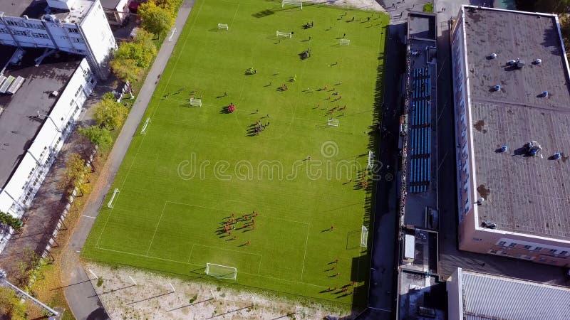Fußballspieler, die um den Fußballplatz laufen Draufsicht des Fußballjugendturniers lizenzfreies stockfoto