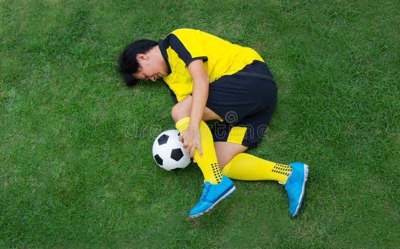 Fußballspieler im gelben Lügen verletzt auf der Neigung stockbild