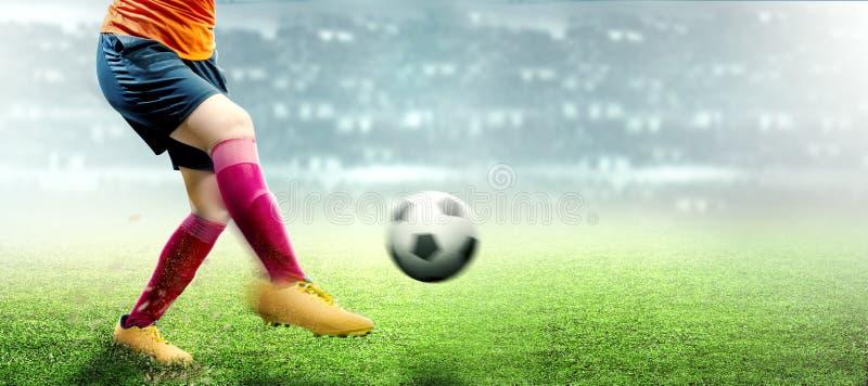 Fußballspielerfrau im orange Trikot, das den Ball tritt stockfotos