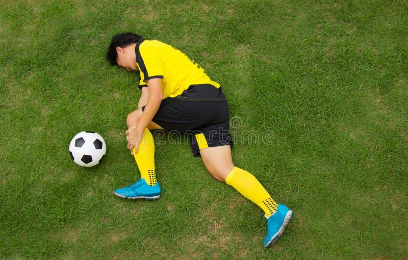 Fußballspielerlügen verletzt auf der Neigung stockfoto