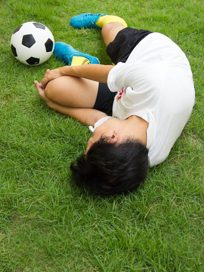 Fußballspielerlügen verletzt auf der Neigung stockbilder
