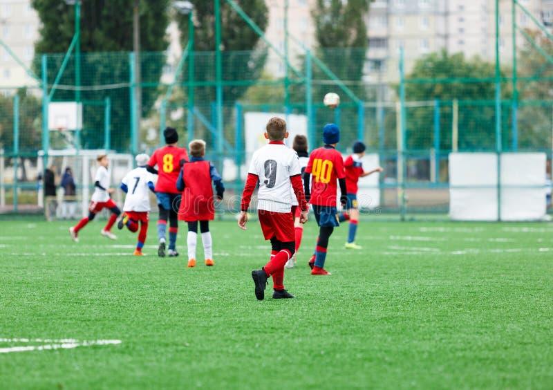Fußballteams - Jungen im roten, blauen, weißen einheitlichen Spielfußball auf dem grünen Feld tröpfelnde Jungen Teamspiel, Traini lizenzfreies stockbild