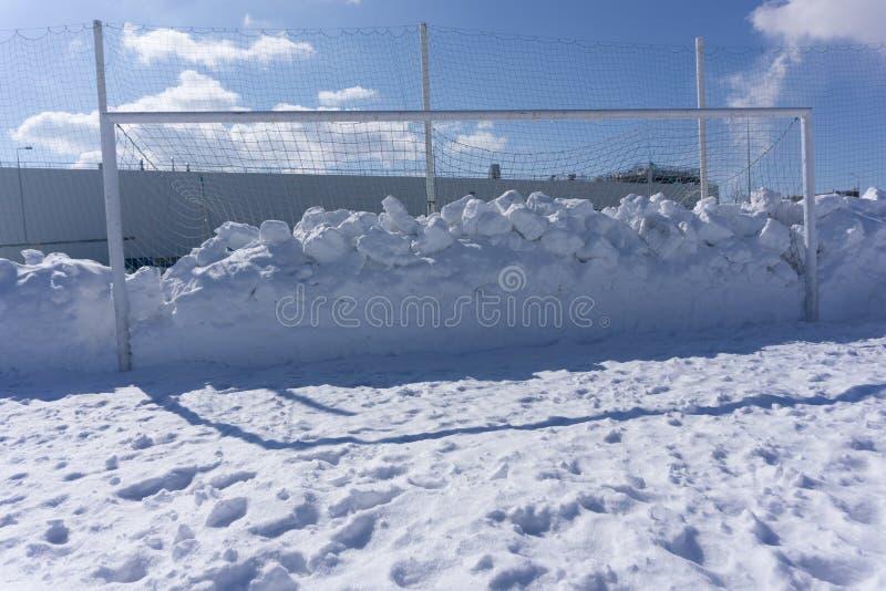 Fußballziel verunreinigt mit Schneewinterfeld stockbilder