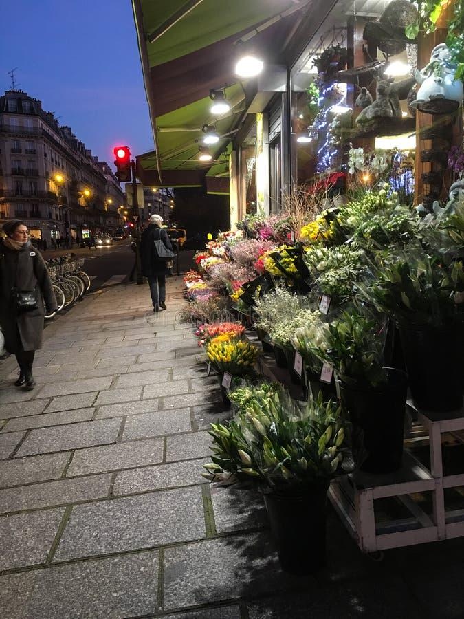 Fußgänger schlendern hinter Paris-Blumengeschäft an einem Winterabend lizenzfreies stockbild