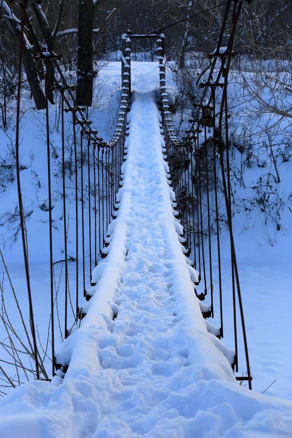 Fußgängerbrücke über Fluss im Winterwald stockfoto