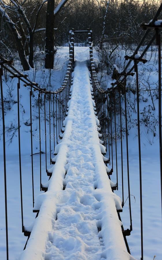 Fußgängerbrücke über Fluss im Winterwald lizenzfreie stockbilder