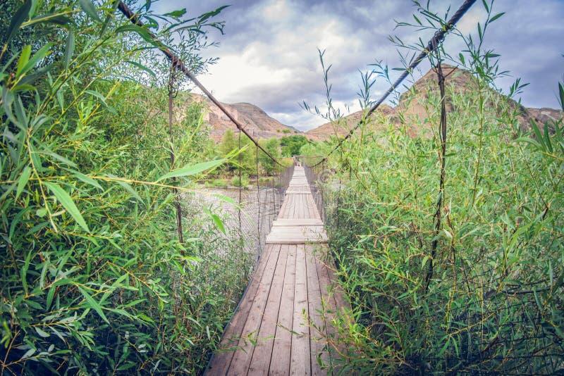 Fußgängerbrücke der alten Suspendierung über Fluss Verzerrungsperspektive fisheye Linse lizenzfreie stockfotografie