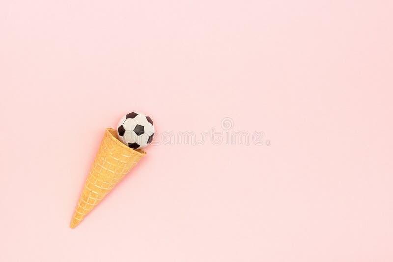 Fußball- oder Fußballball im Eiscreme-Waffelkegel auf rosa Hintergrund in der minimalen Art Konzeptsportunterhaltung Draufsicht K stockfotografie