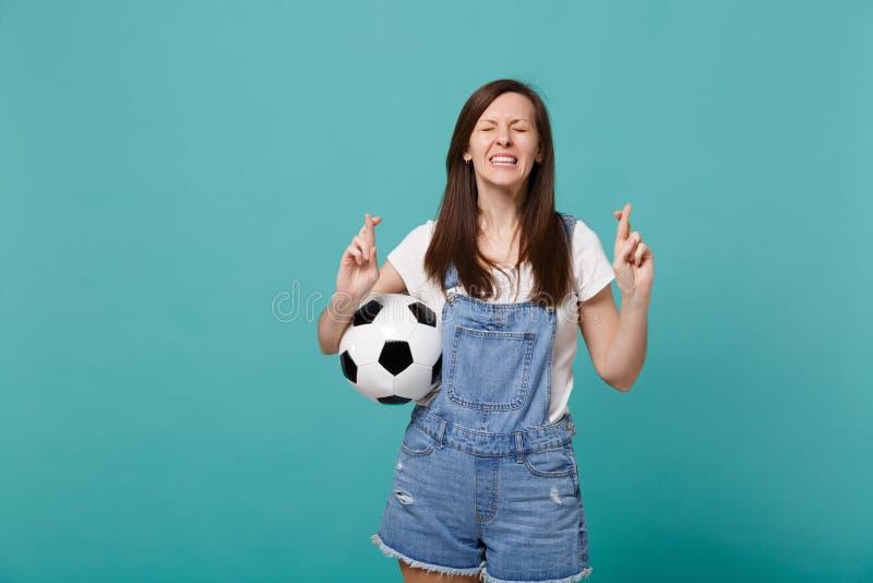 Fußballfanstützlieblingsteam der jungen Frau mit dem Wartespeziellen Moment des Fußballs, der Finger gekreuzt hält lizenzfreie stockfotos
