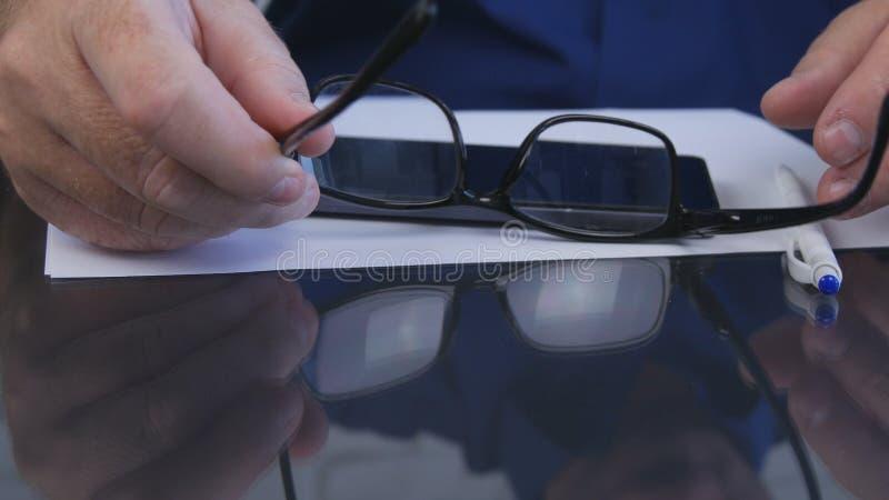 Fucilazione con l'uomo d'affari Hands Taking Eyeglasses dallo scrittorio fotografia stock