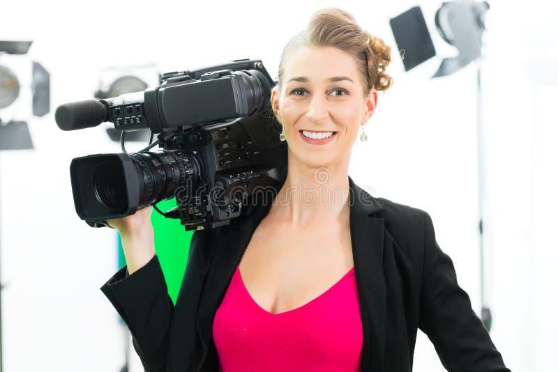 Fucilazione del Camerawoman con la macchina fotografica sull'insieme del film fotografie stock libere da diritti
