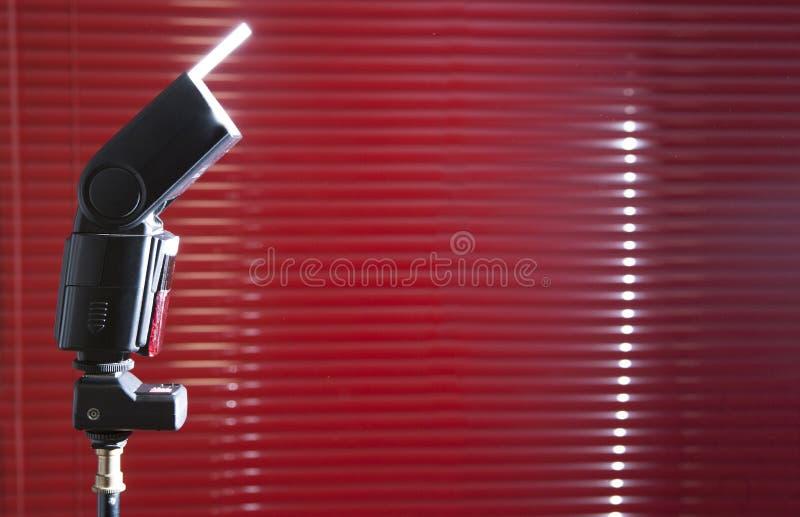 Fucilazione del flashgun di lampeggiatore elettronico con la carta bianca sopra il supporto fotografia stock libera da diritti