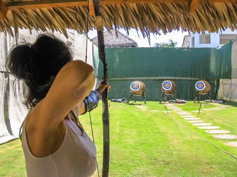 Fucilazione della donna con l'arco fotografia stock libera da diritti