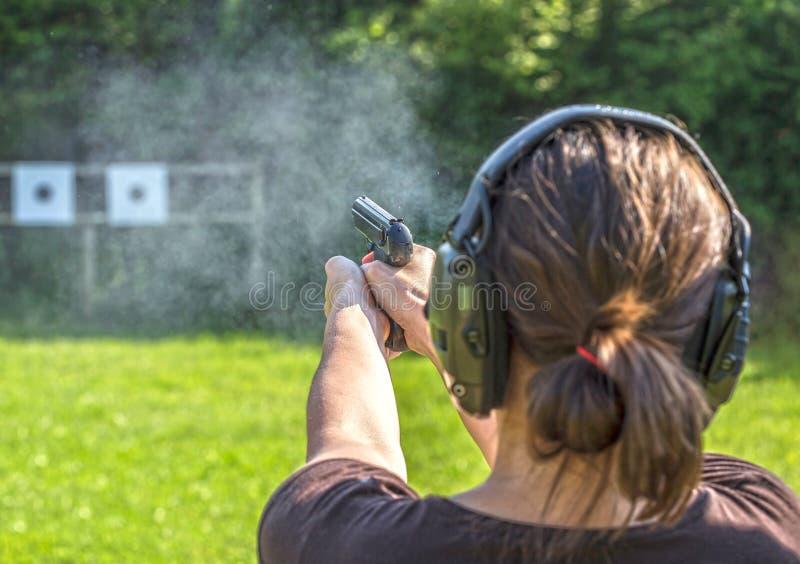 Fucilazione della ragazza con una pistola fotografia stock libera da diritti