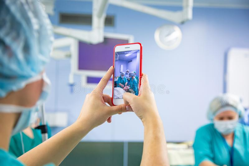 Fucilazione di aiuto sullo smartphone dalla sala operatoria Team Performing Surgical Operation medico in moderno immagini stock libere da diritti