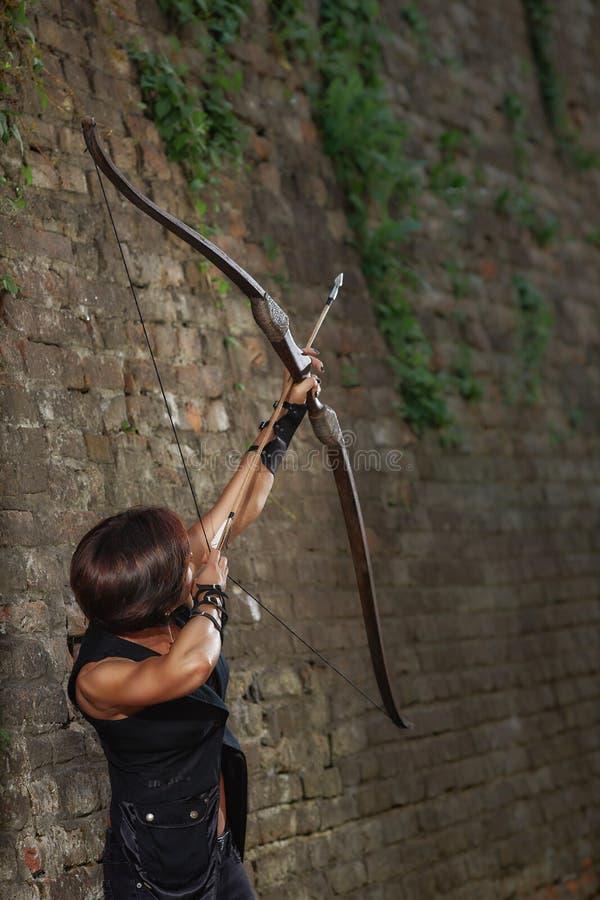 Fucilazione femminile del guerriero dall'arco al cielo fotografia stock