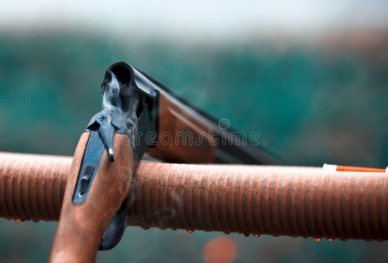Fucile da caccia di caccia con la pioggia di goccia delle cartucce delle pallottole Fumo fotografia stock