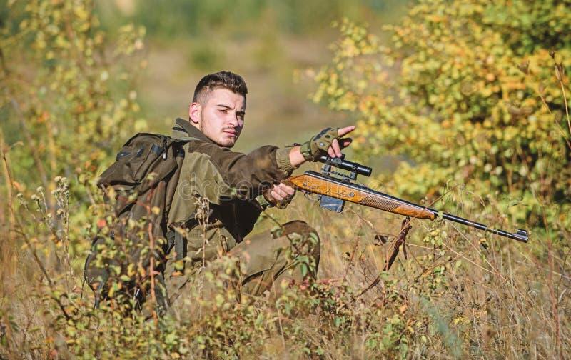 Fucile della tenuta del cacciatore L'uomo indossa il fondo della natura dei vestiti del cammuffamento Cercare permesso Cacciatore fotografie stock