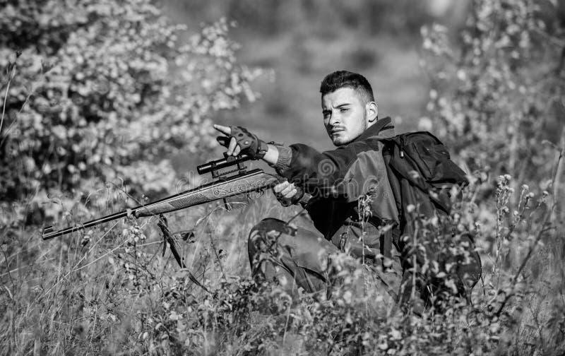 Fucile della tenuta del cacciatore L'uomo indossa il fondo della natura dei vestiti del cammuffamento Cercare permesso Cacciatore immagini stock
