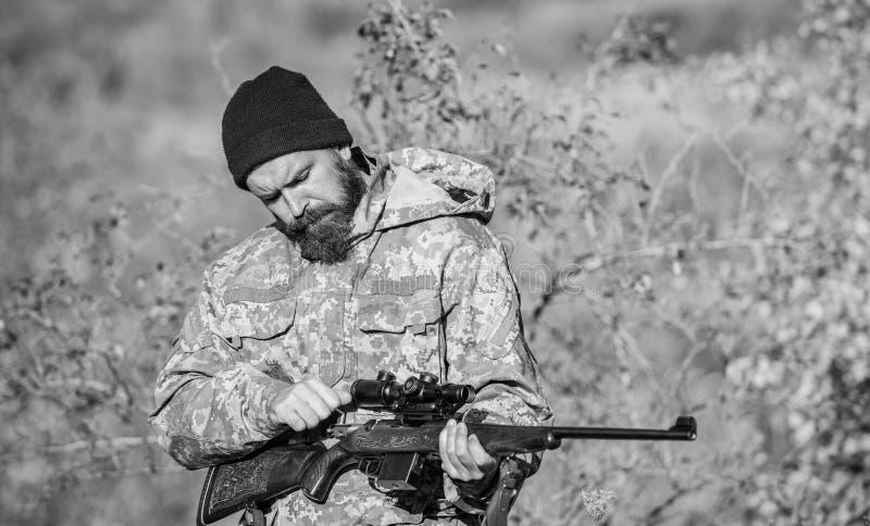 Fucile della tenuta del cacciatore Tendenza delle abilit? Cercare permesso Cacciatore barbuto spendere caccia di svago Cercare at fotografia stock