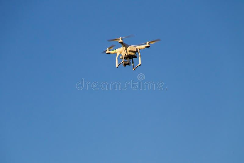 Fuco di Quadcopter con la macchina fotografica che si libra in cielo blu fotografia stock libera da diritti
