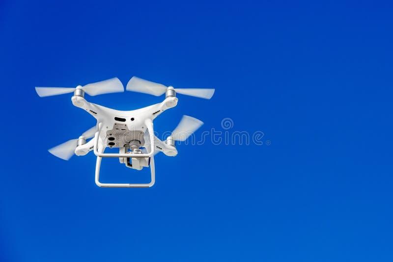 Fuco di Quadcopter con la macchina fotografica contro il cielo blu immagine stock