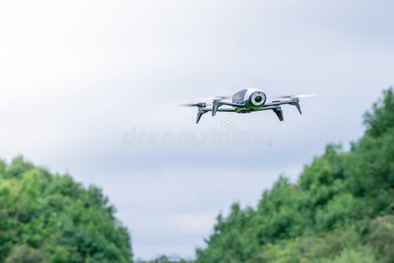 Fuco nero della macchina fotografica nel volo con il movimento visibile delle eliche e nel fondo del cielo blu immagine stock libera da diritti