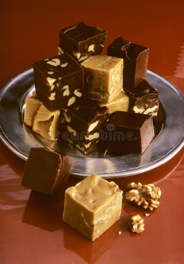Fudge on brown. Multi colored fudge on silver plate on brown royalty free stock photo