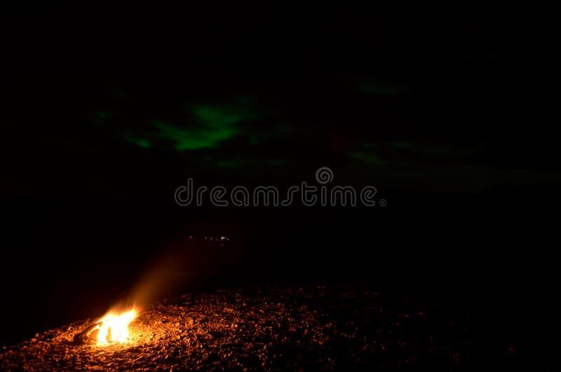 Fuego ardiente caliente en orilla del río con aurora borealis en el cielo foto de archivo libre de regalías