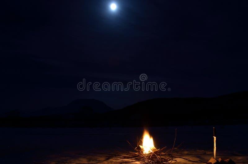 Fuego ardiente en cama de río congelada con la montaña nevosa majestuosa y la Luna Llena foto de archivo