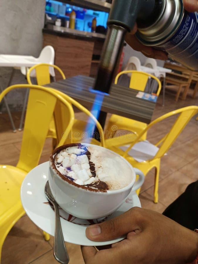 Fuego de la antorcha en la taza del chocolate caliente con los mashmallows mientras que mano que sostiene la taza de las bebidas imagenes de archivo