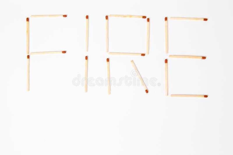 FUEGO de la inscripción escrito con los partidos de madera - para mantener fuera del alcance de niños foto de archivo