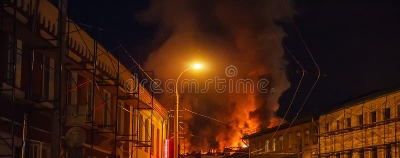 Fuego de la noche en la construcción de viviendas Concepto de la tragedia del desastre y del accidente del fuego imagen de archivo