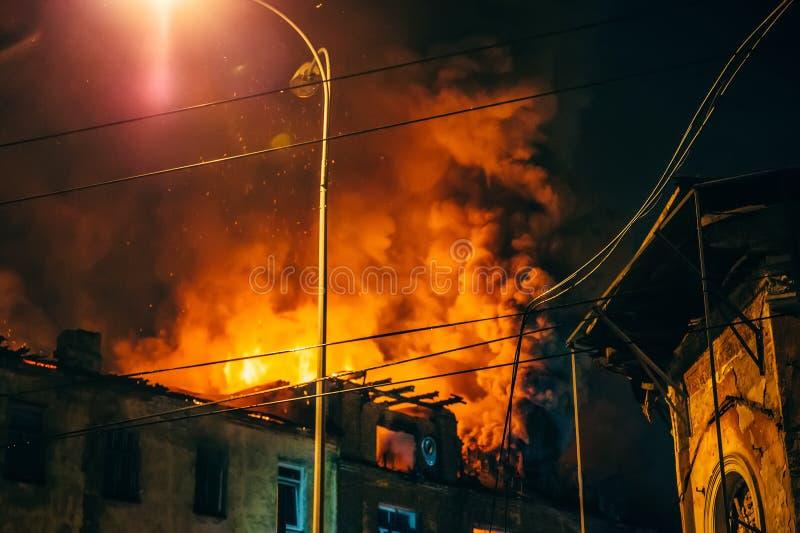 Fuego de la noche en el tejado en la construcción de viviendas, casa ardiente con humo enorme, desastre del fuego y tragedia del  foto de archivo