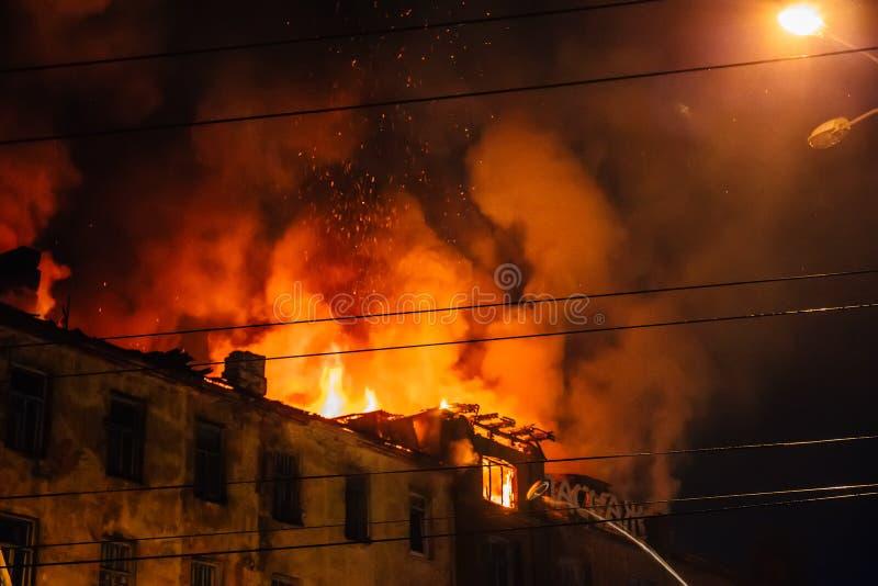 Fuego de la noche en el tejado en la construcción de viviendas, casa ardiente con humo enorme, desastre del fuego y tragedia del  fotografía de archivo