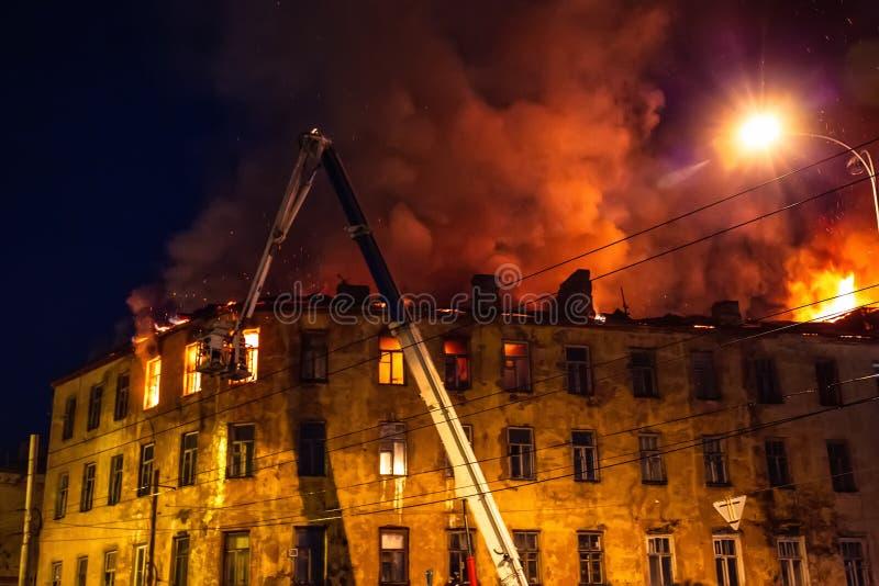 Fuego de la noche en el tejado en la construcción de viviendas, casa ardiente con humo enorme, desastre del fuego y tragedia del  imágenes de archivo libres de regalías