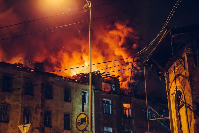 Fuego de la noche en el tejado en la construcción de viviendas, casa ardiente con humo enorme, desastre del fuego y tragedia del  fotografía de archivo libre de regalías