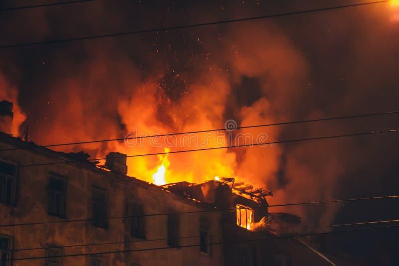 Fuego de la noche en el tejado en el edificio, casa ardiente con humo, desastre del fuego y tragedia del accidente foto de archivo libre de regalías