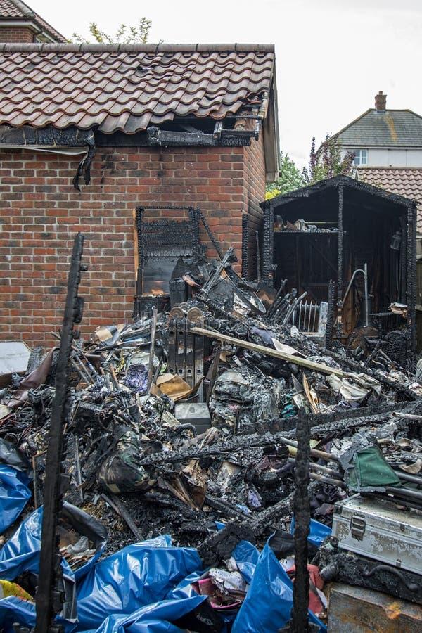 Fuego de la vertiente del jardín Restos carbonizados y daño del garaje de la casa fotografía de archivo