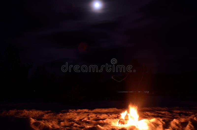 Fuego de registro del abedul en nieve del invierno en una noche oscura de la Luna Llena foto de archivo libre de regalías