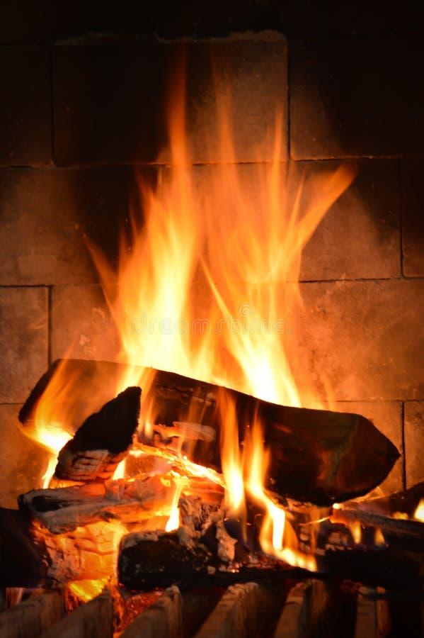 Fuego del rugido en chimenea con los registros y las llamas imágenes de archivo libres de regalías