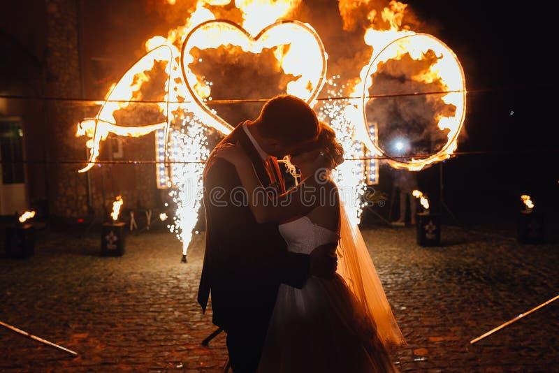 Fuego-demostración que se besa y de observación de los pares cariñosos de la boda foto de archivo