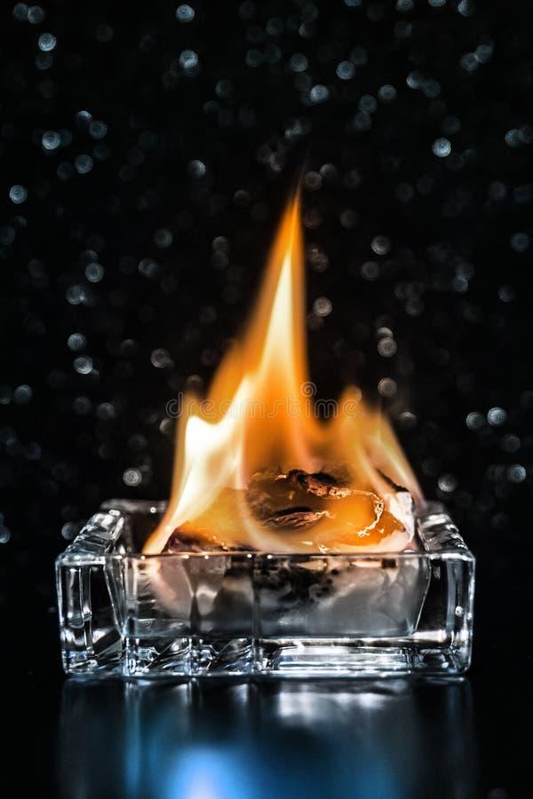 Fuego dentro del cenicero de cristal cuadrado en la oscuridad imagen de archivo libre de regalías