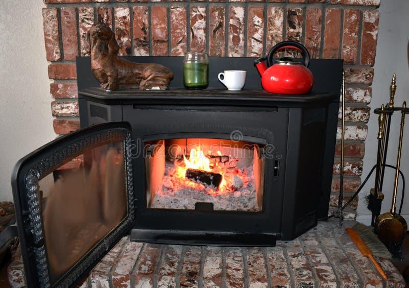 Fuego en chimenea del ladrillo y capa dentro de una sala de estar acogedora imagen de archivo libre de regalías