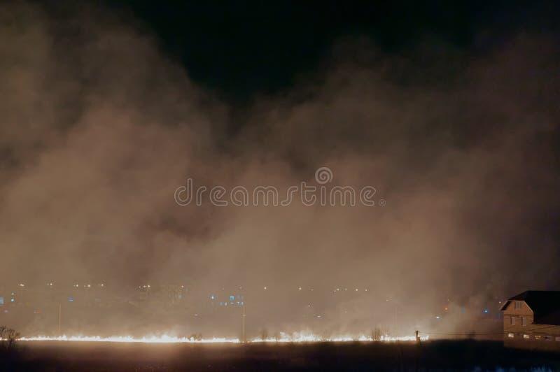 Fuego en el campo en la noche, hierba ardiente en el campo, el humo del campo ardiente imágenes de archivo libres de regalías