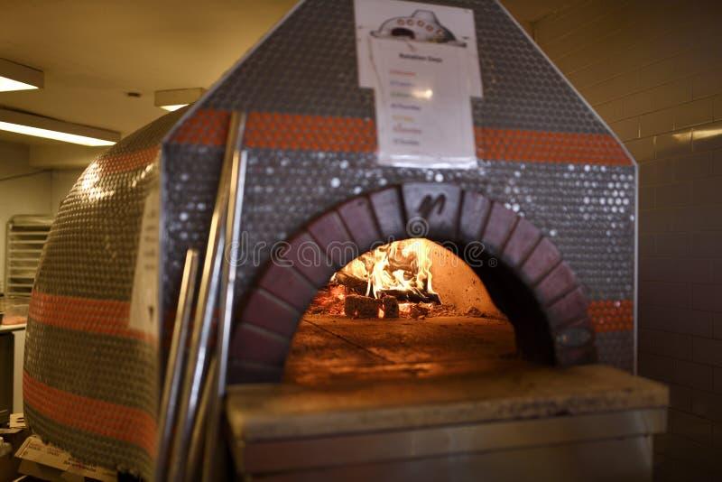 Fuego en horno ardiente de madera de cerámica de la pizza de la bóveda en la cocina de A imágenes de archivo libres de regalías