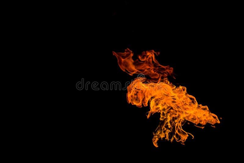 Fuego en la forma de un UFO del extranjero con las alas La llama en el fondo negro se aísla fotos de archivo
