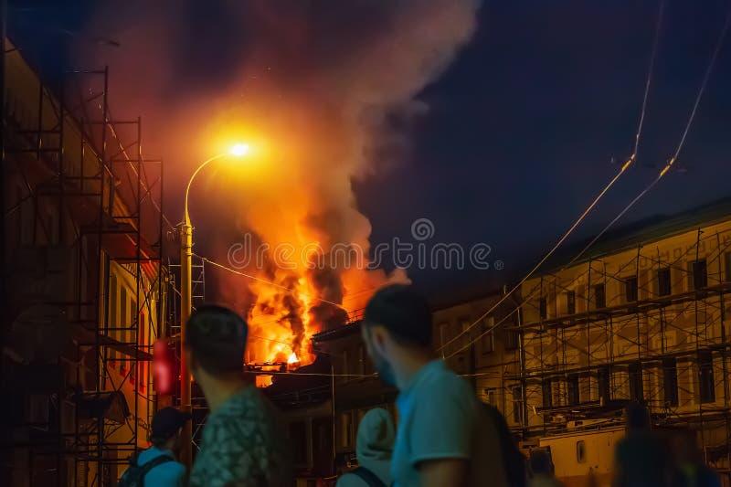 Fuego en noche, tejado constructivo ardiendo y gente borrosa en accidente de observación del primero plano en calle de la ciudad imágenes de archivo libres de regalías
