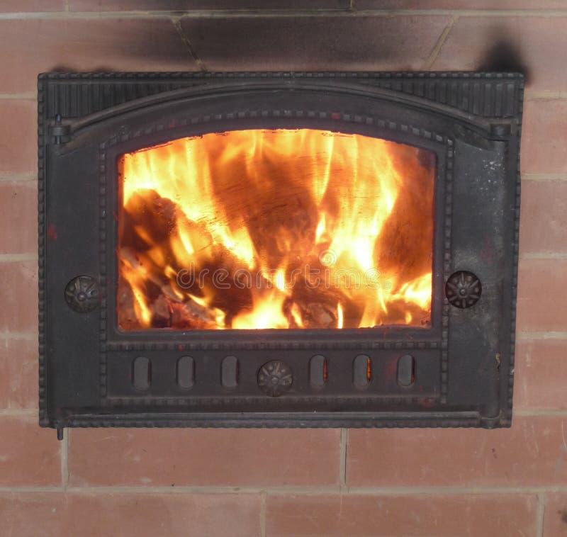 Fuego en una estufa ardiente de madera foto de archivo