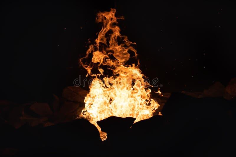 Fuego en una piedra Firepit en la noche imagen de archivo